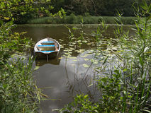 Row boat in small lake. Row boat alone in small lake, pond. Oars lying in boat. Surrounded by water lilies and lush green vegetation Stock Photos