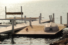 A row boat up side down on a lake dock Stock Images