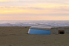 Row boat upside down on a winter shore at sunset Royalty Free Stock Photo