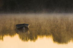 Row Boat on Water at Dawn. An aluminum row boat moored offshore on a lake at sunrise with fog rising off the lake and trees reflected on the waters surface stock photos