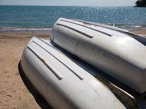 Row boats on a beach. Row boats stashed on a sandy beach near the calm blow water Royalty Free Stock Image
