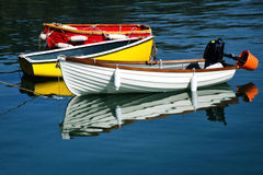 Row-boats. Colourful row-boats with mirror-like reflections at the harbour Royalty Free Stock Photo