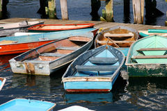 Row boats and dinghies. Row boats tied to old dock located in Maine, USA Stock Photos