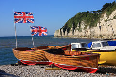 Row boats for hire. Patriotic row boats with Union Jack flags fluttering in the wind available for hire on a Devon beach stock photos