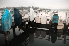 Row boats tied to jetty handrails. Royalty Free Stock Photo