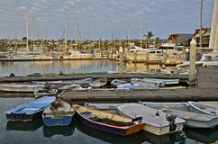 Row Boats and Yachts in a Harbor. Row boats are secured to a dock in a fishing harbor in San Diego with many yachts in the background Royalty Free Stock Photos