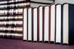 Row of books background. Books tile. Leather, hardcover, new books in a row. Crisp new white paper stock images