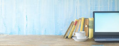 Books, cup of coffee and laptop, learning, education. Row of books, cup of coffee and laptop, learning, education, panorama, copy space royalty free stock images