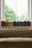 Row Of Books On Windowsill With Sofa In Foreground Stock Image