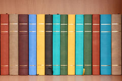Row of books in wooden cabinet. Stock Photo