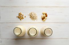 Row of Bottled Milk Substitutes with Ingredients on White Wood P Royalty Free Stock Images
