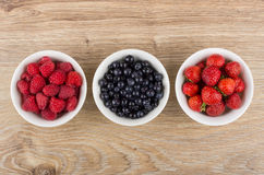 Row of bowls with raspberries, blueberries and strawberries on t Stock Images
