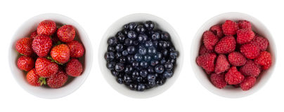 Row of bowls with raspberries, blueberries and strawberries on w. Row of bowls with raspberries, blueberries and strawberries isolated on white background. Top Stock Photos