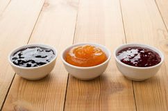 Row of bowls with raspberry, peach, blueberry jam on table Royalty Free Stock Photos