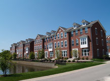 Row of Brick Condos With Bay Windows. A row of brick condos or townhouses with bay windows beside a street Stock Image