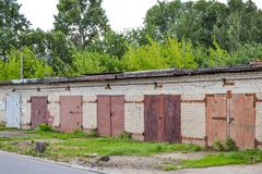 A row of brick garages with rusty metal gates. Russia stock photos
