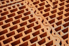 Row of bricks in red  color with the inner holes in the shape of honeycomb on the construction site. Row of bricks in red and orange color with the inner holes Royalty Free Stock Photo