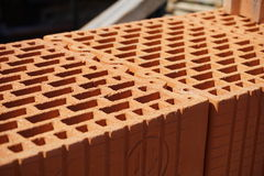 Row of bricks in red  color with the inner holes in the shape of honeycomb on the construction site. Row of bricks in red and orange color with the inner holes Stock Image