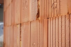 Row of bricks in red  color with the inner holes in the shape of honeycomb on the construction site. Row of bricks in red and orange color with the inner holes Stock Photography