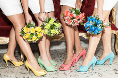 Row of bridesmaids with bouquets of flowers and shoes of different colors. Bridesmaids wedding day showing his shoe and floral arrangements of different colors stock photos