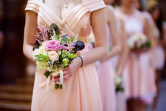 Row of bridesmaids with bouquets at wedding Royalty Free Stock Image
