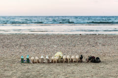 A row of bridesmaids and groomsmen shoes and a bride`s bouquet o. N the beach in summer. Outdoor shot with natural light Royalty Free Stock Photo