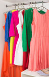 Row of bright colorful dress hanging on coat hanger, shoes  Stock Image