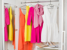 Row of bright colorful dress hanging on coat hanger, shoes and h Royalty Free Stock Image