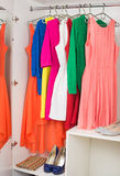 Row of bright colorful dress hanging on coat hanger, shoes and h Royalty Free Stock Photo