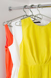 Row of bright colorful dress hanging on coat hanger in white war Royalty Free Stock Image