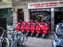 Row of bright red motor scooters parked outside dealership on sidewalk in Paris Royalty Free Stock Photography