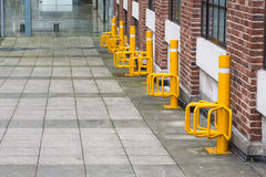 A row of bright yellow bicycle parking points. Yellow bike parking outside a shopping centre Royalty Free Stock Photos