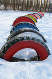 Row of brightly colored tires in snow, Russia. Royalty Free Stock Photos
