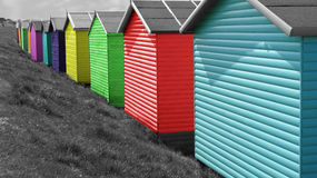 Row of brightly coloured beach huts. Photo of a row of brightly multi-coloured beach huts on black and white background stock image