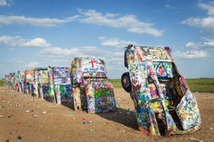 Row of brightly painted Cadillacs in the Cadillac Ranch in Amarillo, Texas, USA. Amarillo, Texas - July 8, 2014: Row of brightly painted Cadillacs in the Royalty Free Stock Images