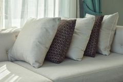 Row of brown and white pillows on beige sofa. Next to the window Stock Image