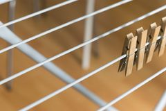 Row Brown Wooden Pegs Clipped Collapsible Clotheshorse Brown Wooden Background.  Stock Photo