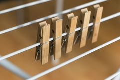 Row Brown Wooden Pegs Clipped Collapsible Clotheshorse Brown Wooden Background.  Royalty Free Stock Image