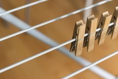 Row Brown Wooden Pegs Clipped Collapsible Clotheshorse Brown Wooden Background.  Royalty Free Stock Photography