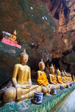 A row of Buddha statues in the cave Stock Photos