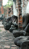 A row of Buddha statues. A row of headless buddha statues against a crumbling brick wall Royalty Free Stock Images