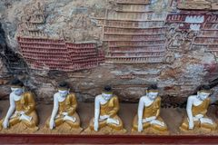 Row of Buddha statues in Kaw Goon cave with. Royalty Free Stock Photo