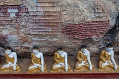 Row of Buddha statues in Kaw Goon cave with. Row of Buddha statues in Kaw Goon cave with carvings in Myanmar. Version 2 Stock Photos