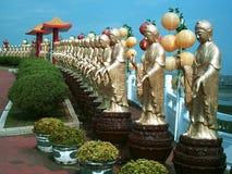 Row of buddhas. A row of buddha statues, holding lanterns stock photos