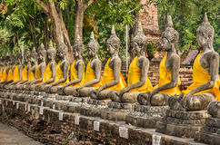 Perspective of Buddha Statues - Wat Yai Chai Mongkol, Ayutthaya. Row of buddhas with yellow clothes in a temple in Ayutthaya, the ancient capital of Thailand Royalty Free Stock Photo