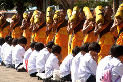 Row of Buddhist hike monks on street. Stock Photos