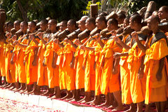 Row of Buddhist hike monks on street. Royalty Free Stock Photography