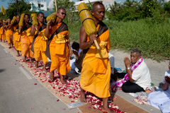 Row of Buddhist hike monks on street. Stock Image