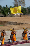 Row of Buddhist hike monks on street. Royalty Free Stock Images