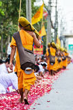 Row of Buddhist hike monks on streets Stock Photo